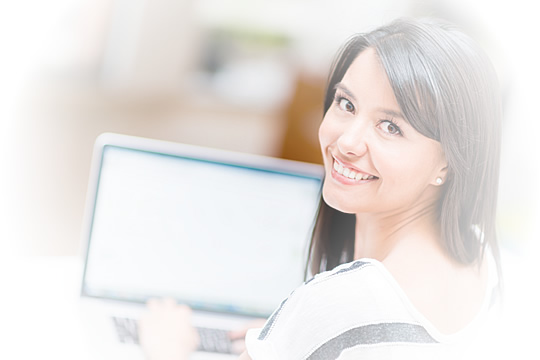 Smiling woman looks over her shoulder, away from computer screen