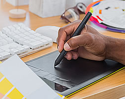 A hand using a stylus on a computer graphics tablet beside colour swatches.